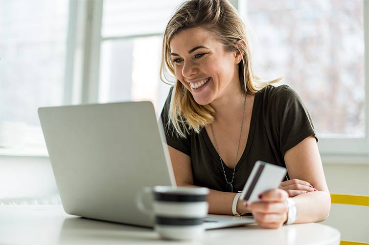 woman holding credit card using laptop