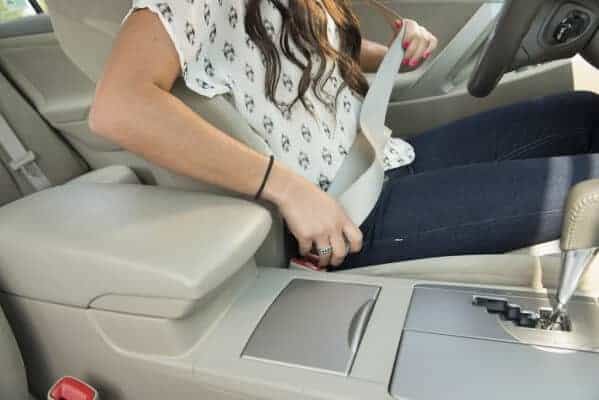 lady putting her seat belt on in car