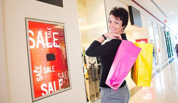 lady holding two shopping bags in front of a sale sign