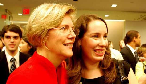 Elizabeth warren taking a photo with a young professional at a conference