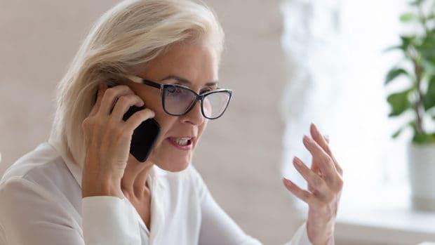 mujer mayor enojada por teléfono; Cómo presentar una queja contra una agencia de cobro de deudas