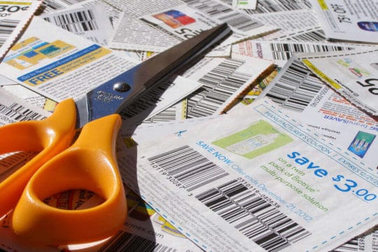 stack of coupons with pair of scissors up top