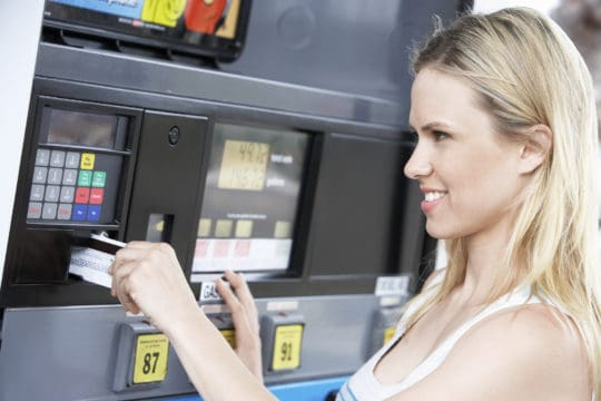 woman at gas pump with credit card