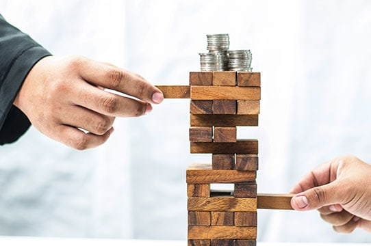 Jenga game tower with stacks of coins on top