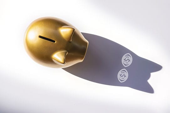 overhead of gold piggy bank. shadow has money signs as eyes