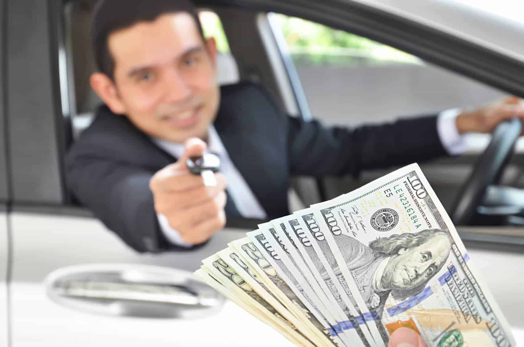 man exchanging keys to car for cash