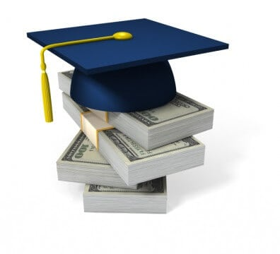 graduation hat on top of stack of cash to show how much student loan debt one is