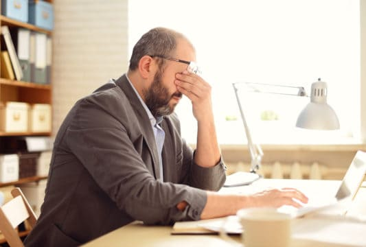 irs tax audit; frustrated man in his office doing taxes
