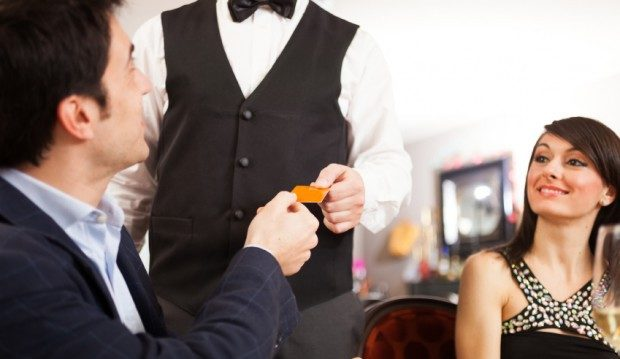 man on a dinner date giving server credit card