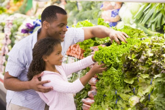 father and daughter at grocery store looking at produce