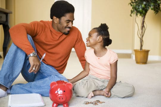 dad sits with daughter on floor, he is teacher her about money with a piggy bank, coins, paper and pen