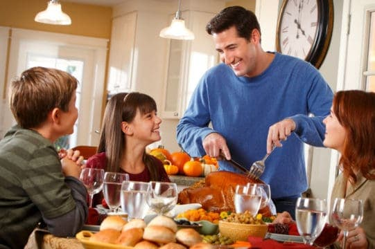 Family at Thanksgiving dinner table, father carving turkey