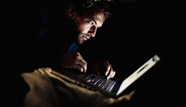 man on his laptop in a dark room