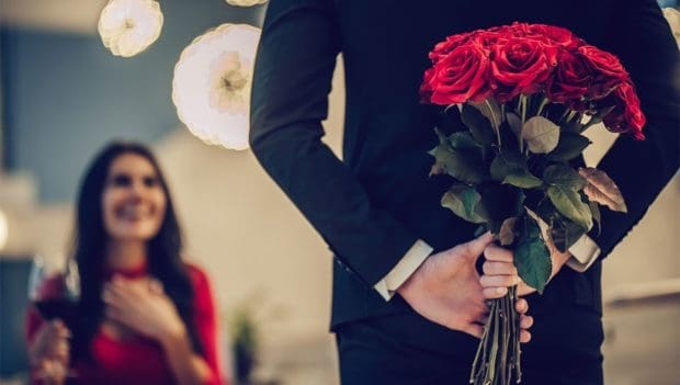 man hiding roses behind his back, woman is excited