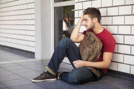 student sitting on the ground leaning on the building looking upset