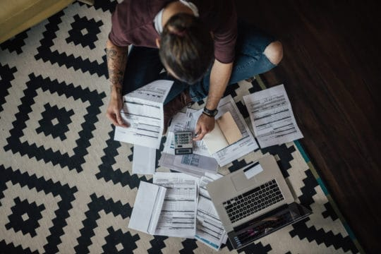 person sitting criss-cross on floor with bills, calculator, and laptop