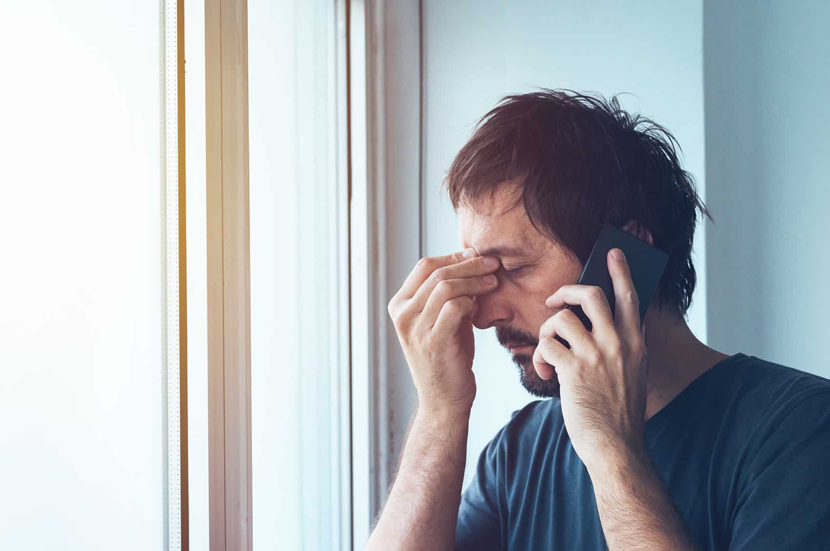 man holding the bridge of his nose as if in stress while he is talking on his cell phone