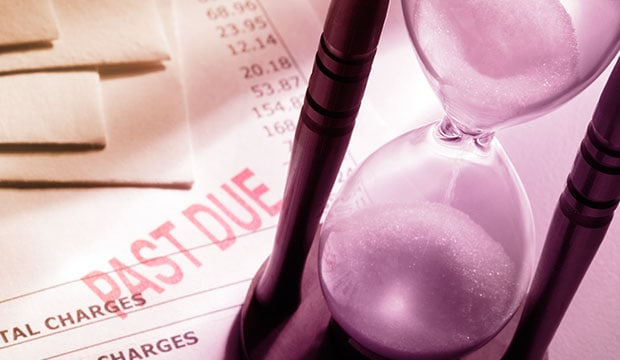 An hourglass counts down on a past due debt