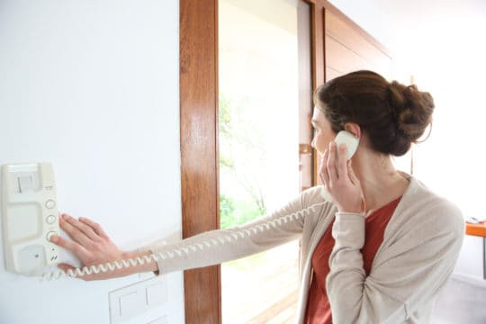 can a debt collector come to my house?; woman answering a security phone while looking out her door