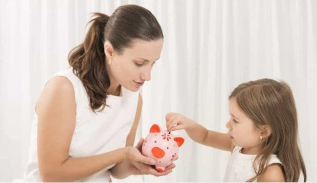 mom holding piggy bank while daughter inserts coins