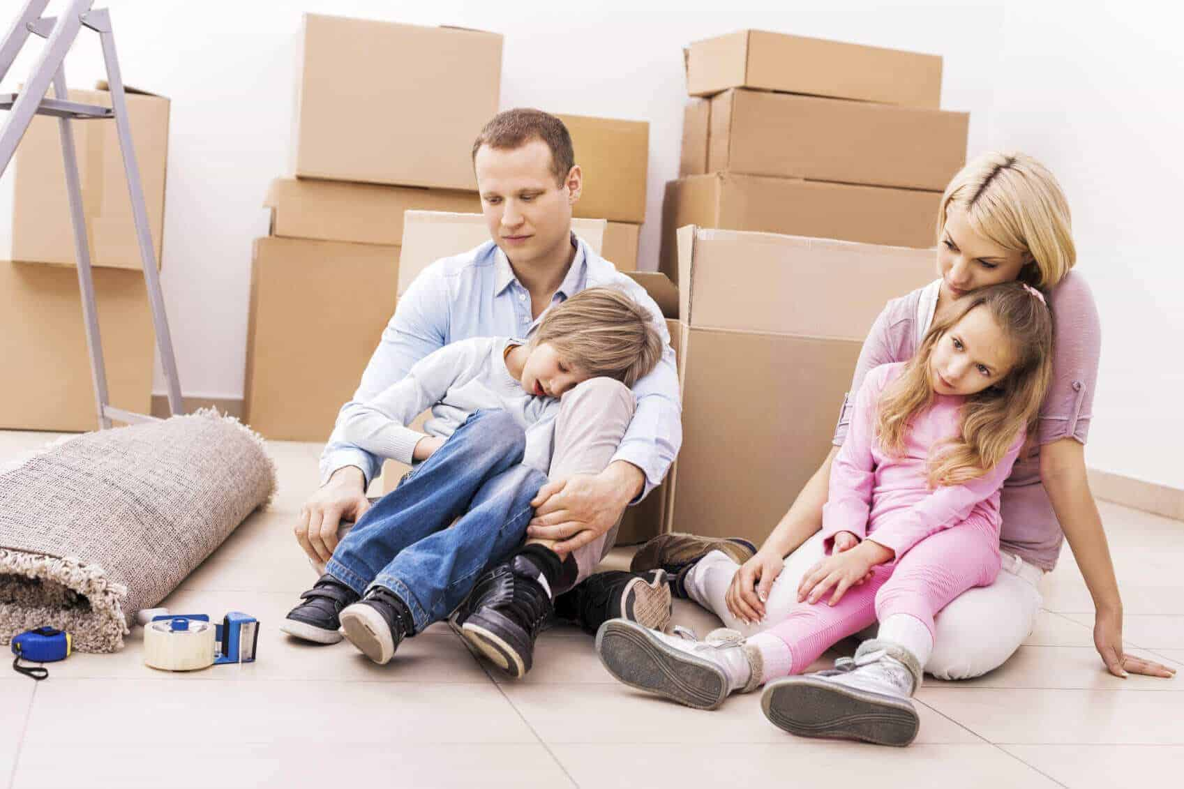 exhausted family sits on the floor surrounded by boxes and packing materials