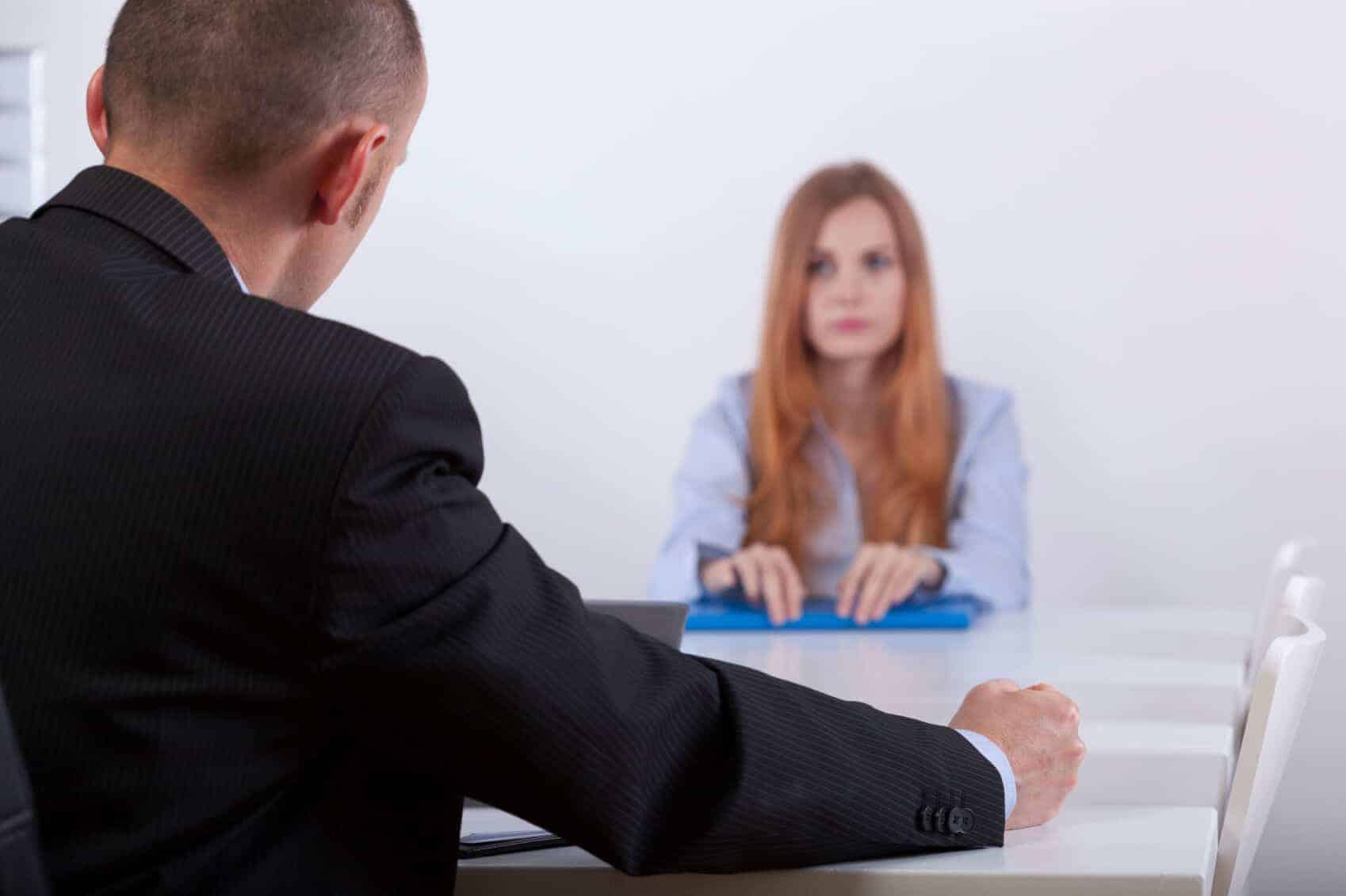 A woman with defensive body language in a job interview
