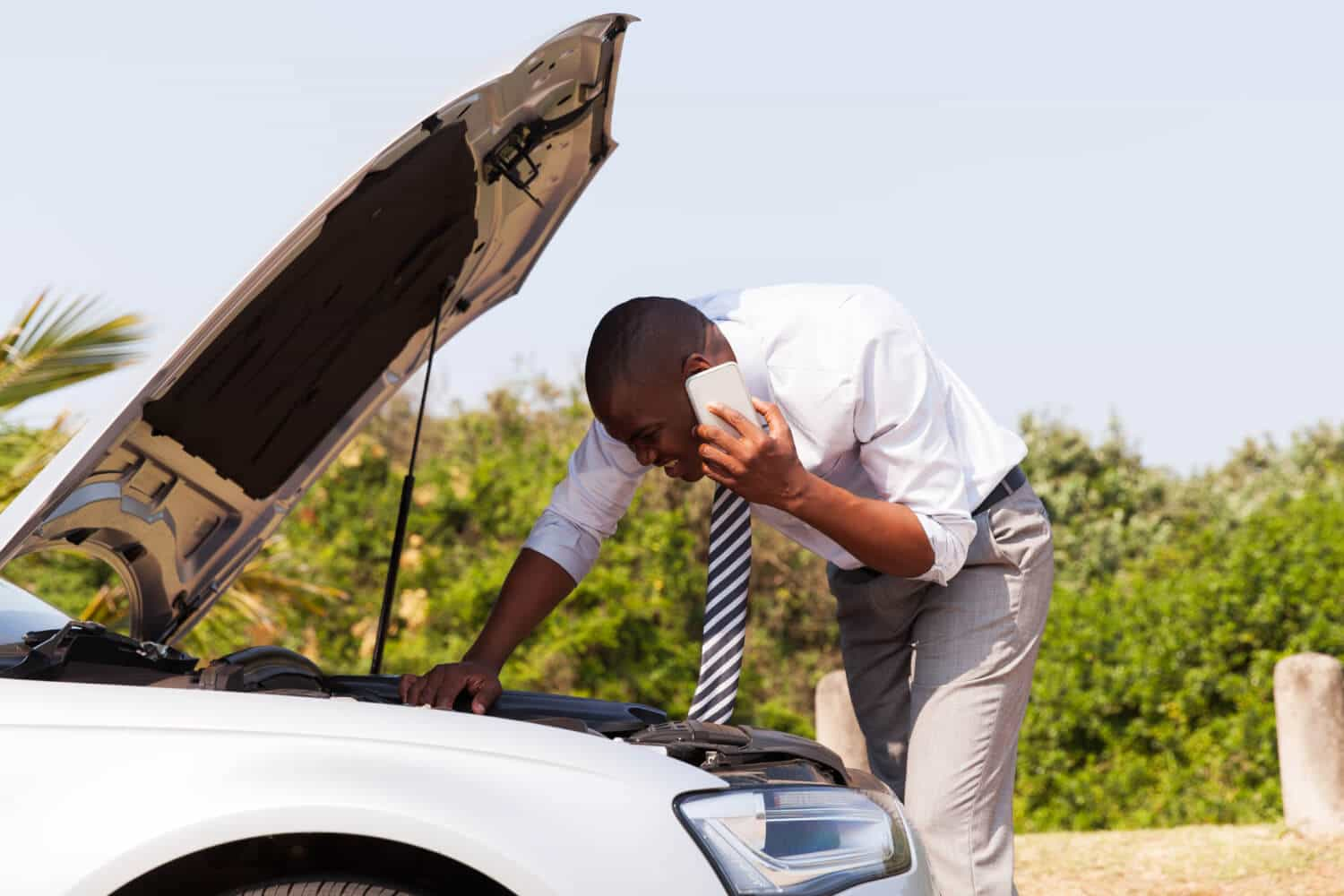 Man with broken down car calls his auto insurance company