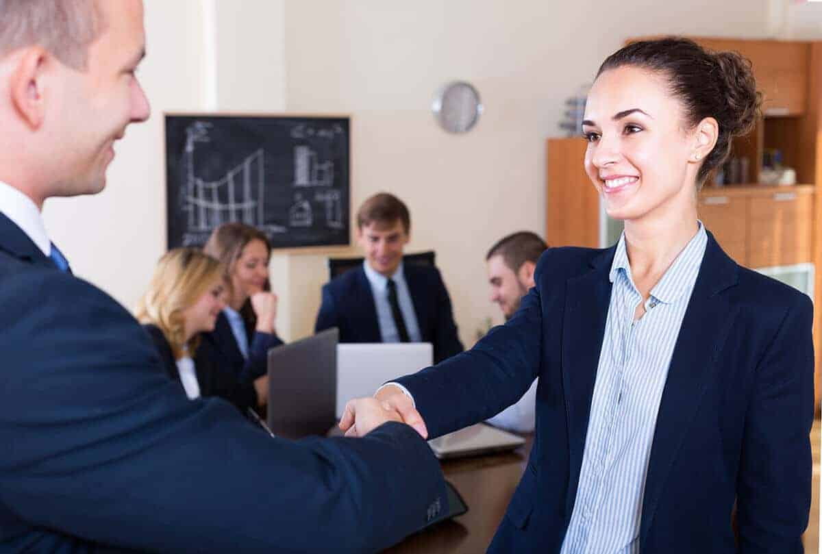 Woman shaking hands with man at a meeting possibly made her career choice based on a movie or TV show