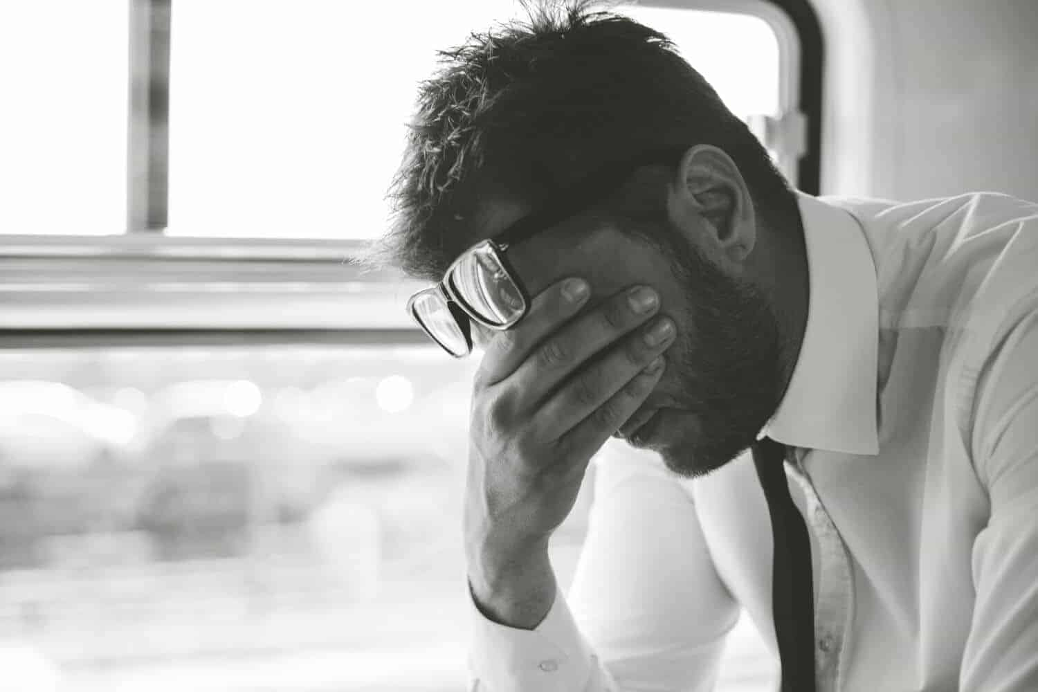 Financial stress upsets business man traveling home by train