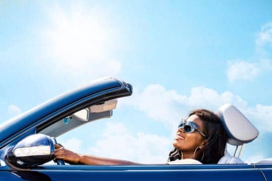 Woman happily driving convertible on a sunny day after she was able to refinance her car loan