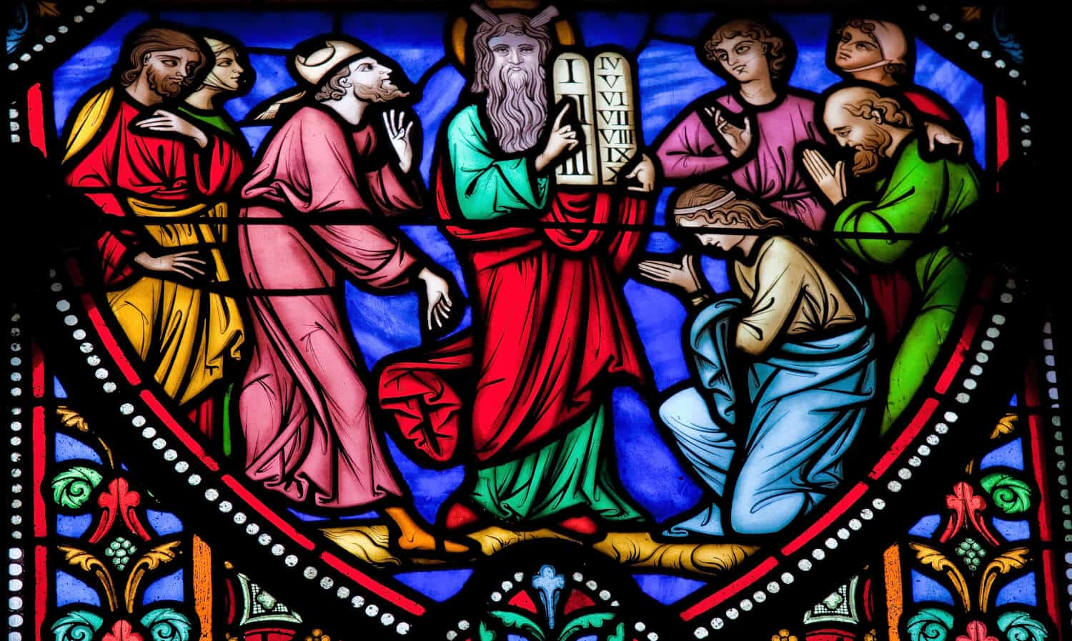 Stained glass window of Moses carrying the 10 Commandments. Which Commandment can predict your debt?