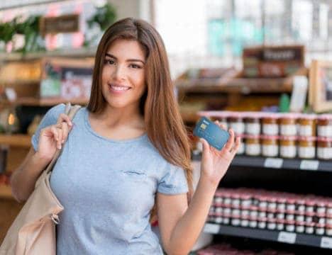 mujer feliz con su tarjeta de crédito