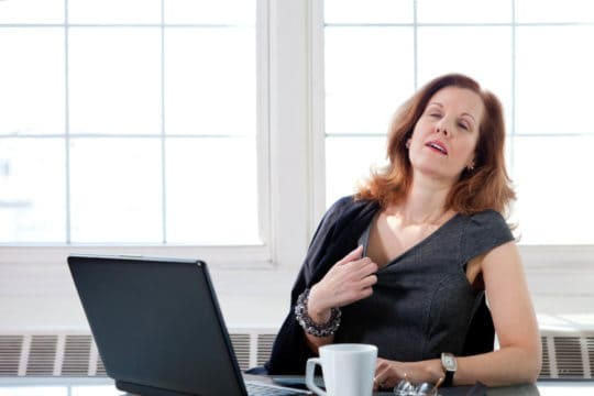 Older business woman gets a menopause hot flash sitting in front of her office computer