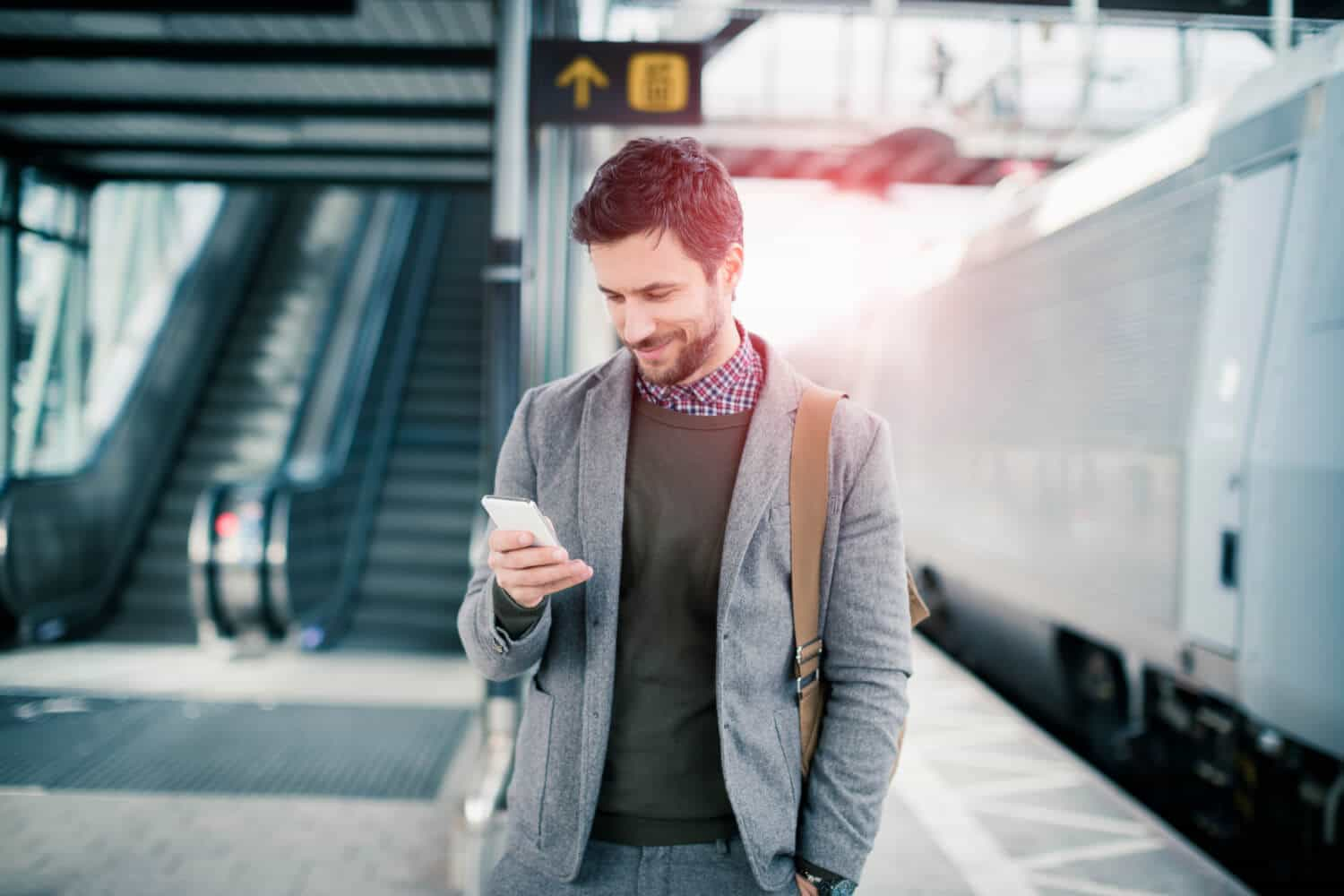 Millennial using his cell phone at the train station believes that retirement sucks