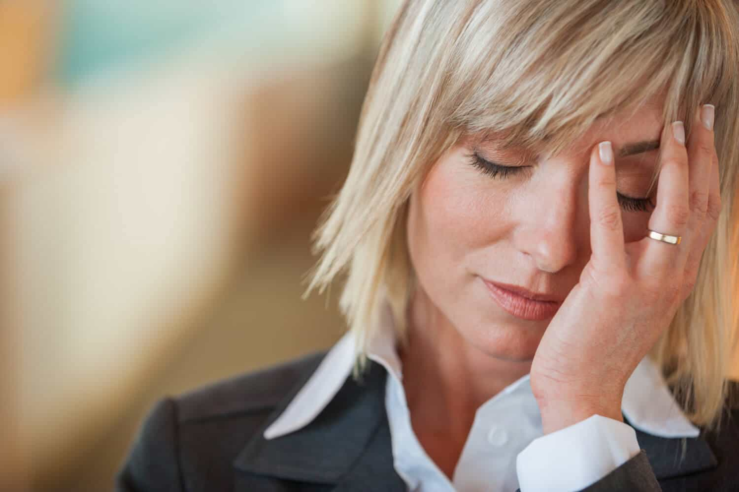 A married business woman places her hand on her face in frustration, uncertain about her debt, budget and finances