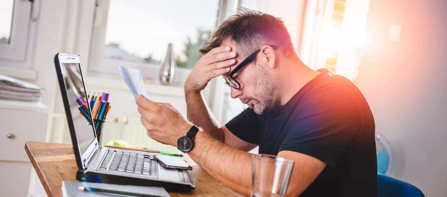 how to get out of a co-signed loan; An older Gen X man sits in front of a laptop looking a bill for a debt he owes, showing signs of financial stress