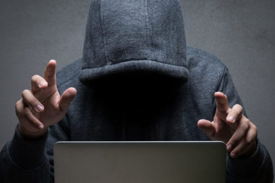 Cyber thief sitting in front of a laptop, poised to steal your identity, personal data, and financial accounts