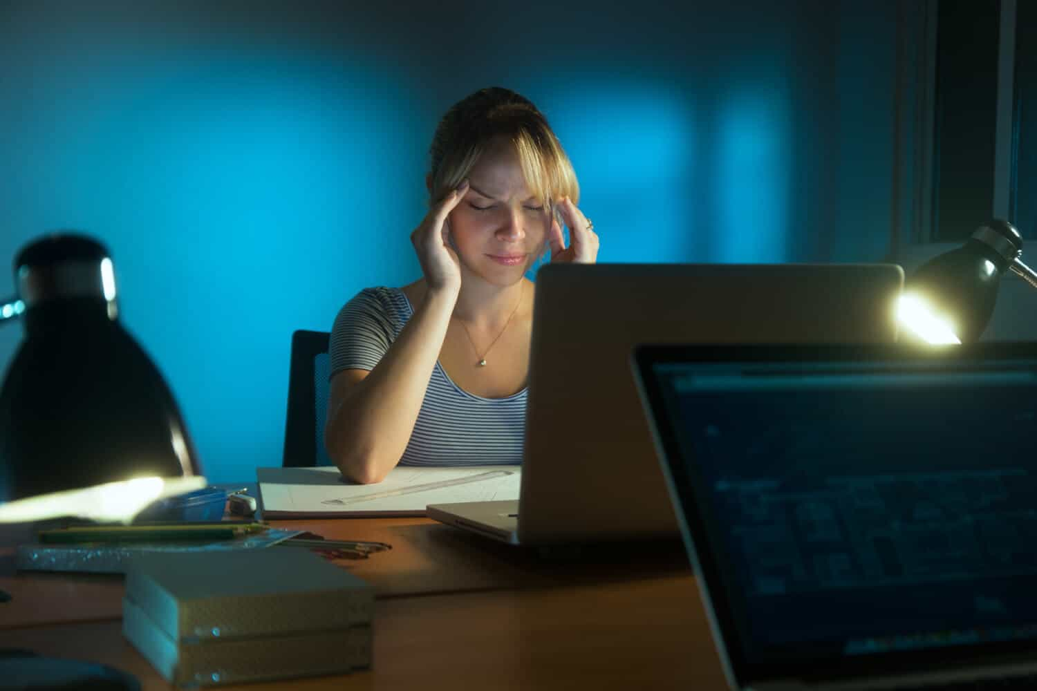 Woman fighting a headache, sitting in front of a laptop in a home office late at night, plagued by financial stress