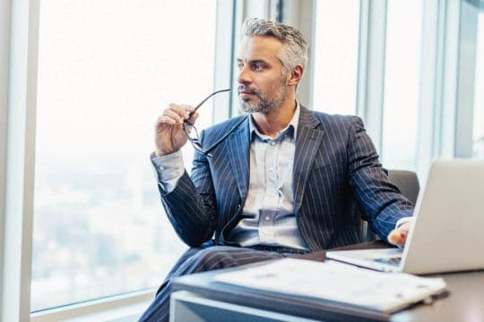 Buisnessman looks out of window while contemplating financial wellness