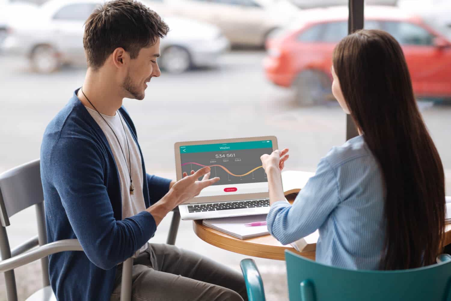 Two Millennials sit at an outdoor cafe looking at a Wallet cash flow graph in a Personal Financial Management (PFM) platform