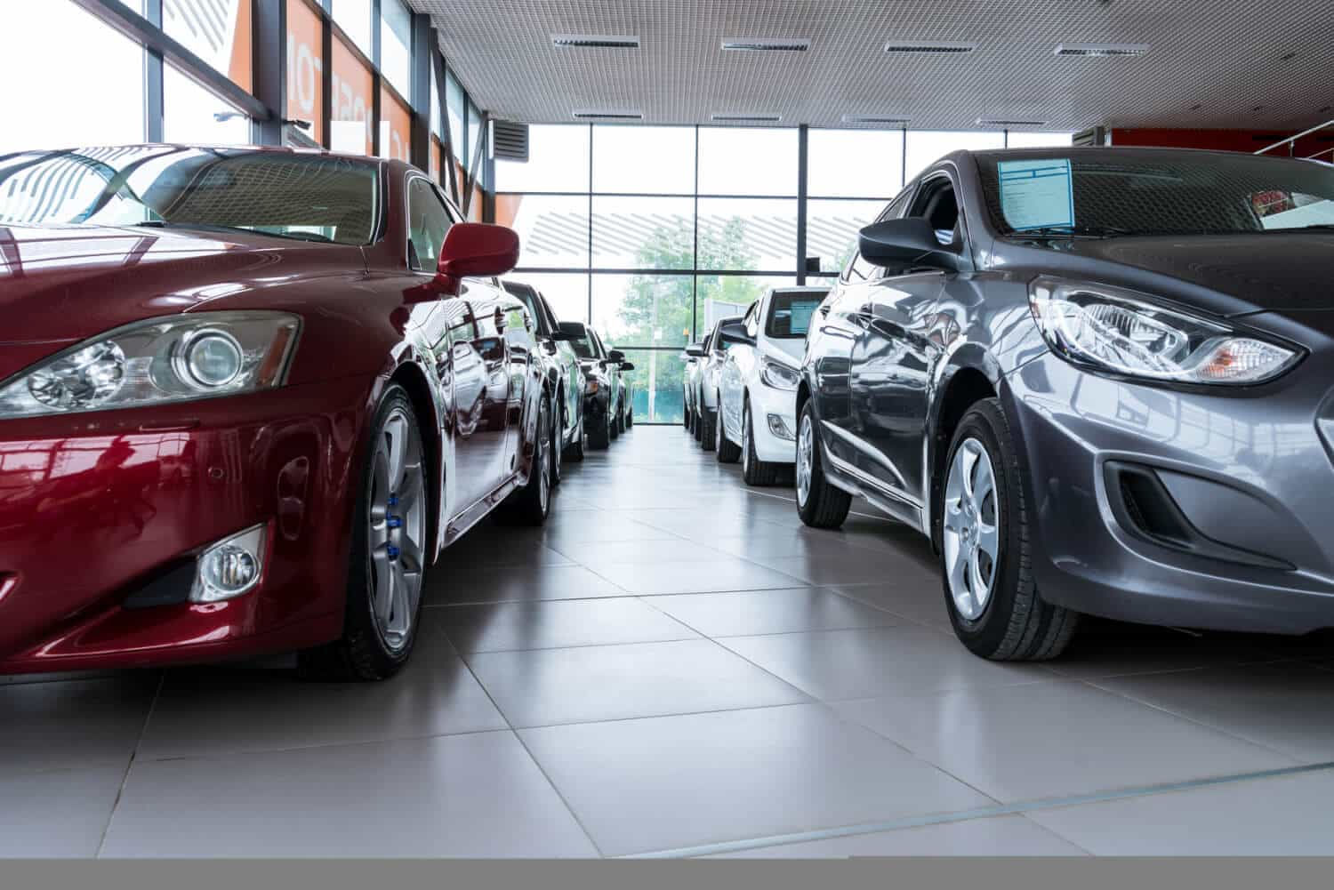 New cars lined up on an auto dealership showroom floor, waiting for car buying financed through auto loans