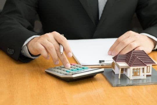 Mortgage loan officer calculates costs on a residential home loan during the underwriting and approval process