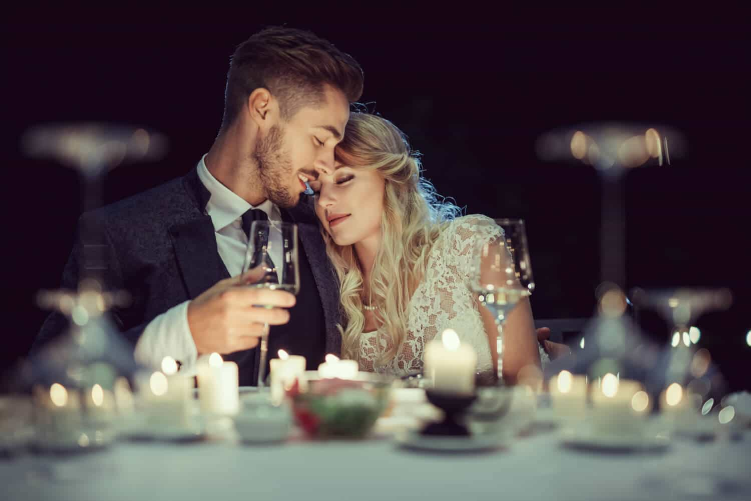 a newlywed couple at a candlelit table