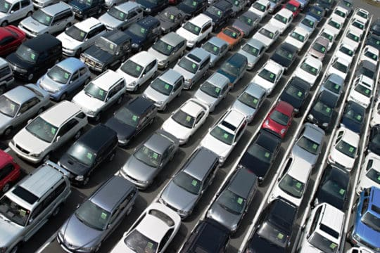 Used cars lined up on an auto dealership car lot, waiting for car buying financed through auto loans