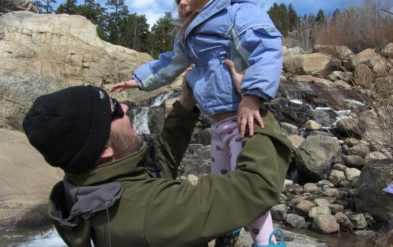 Carl, or Mr. 1500, holds his young daughter in the air