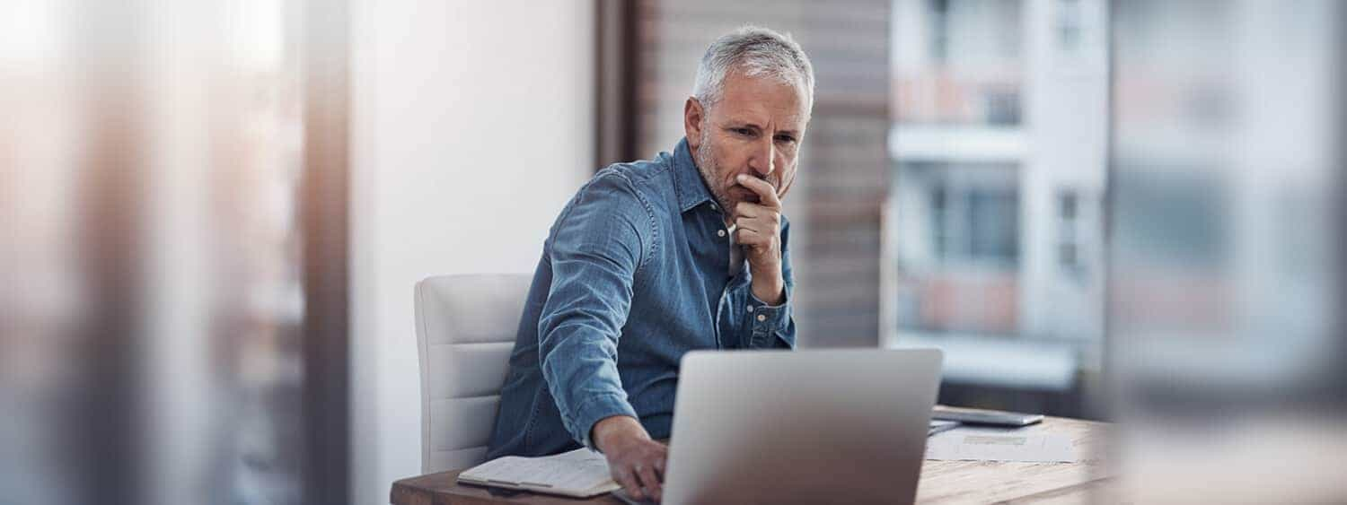 An older man working on his laptop worries about whether he can retire at 65