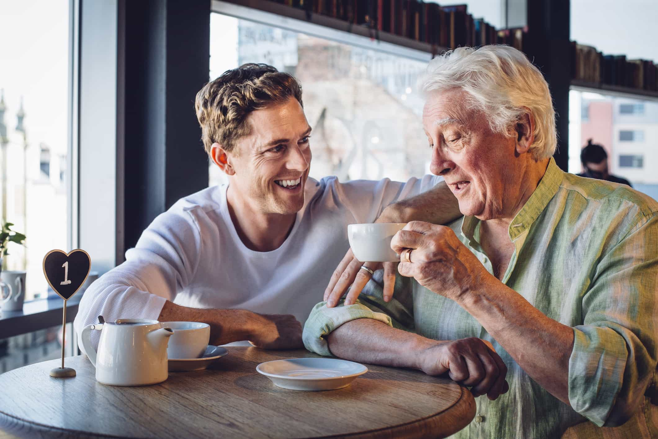 Father and adult son enjoying coffee together