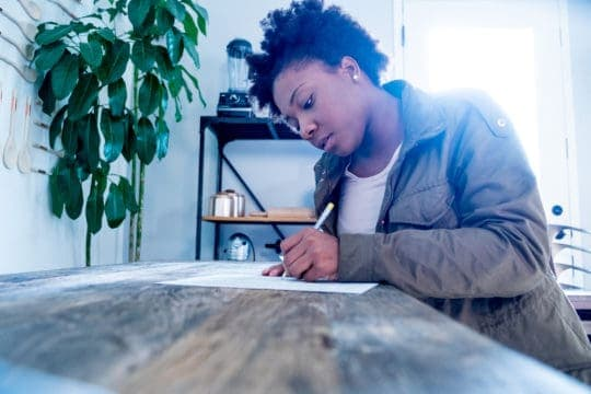 A young black millennial woman fills out a job application