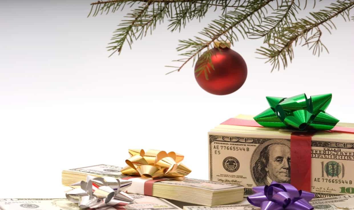 piles of cash tied with bows and ribbon under a Christmas tree