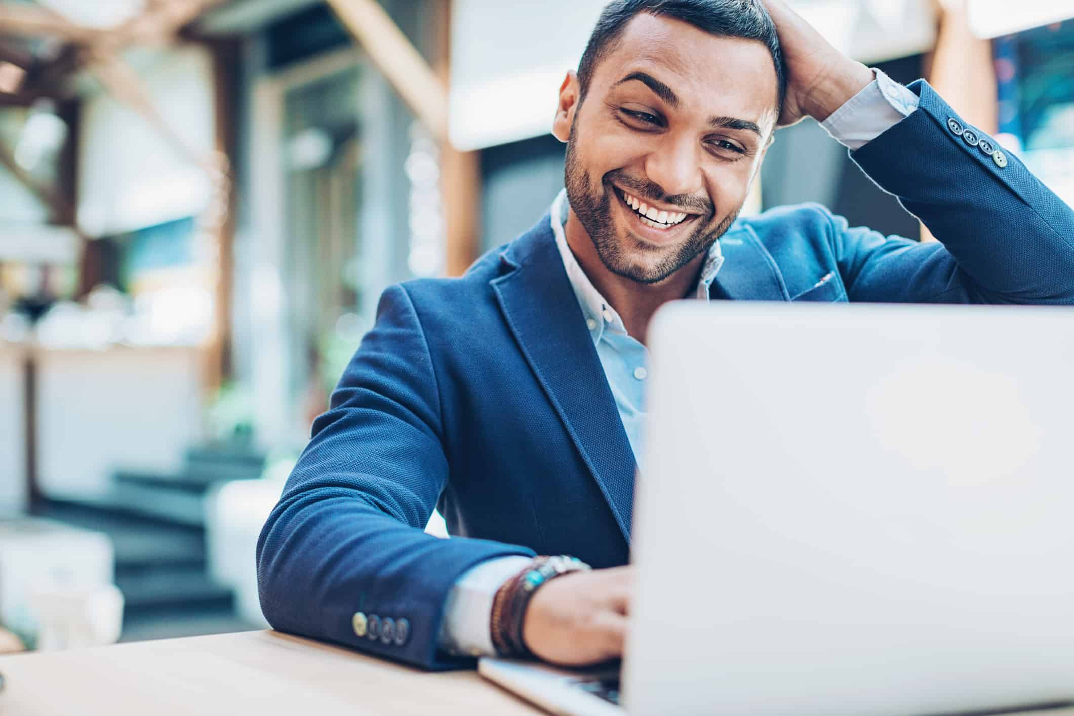 Millennial ready to achieve financial success in 2018 looks at his laptop happily surprised